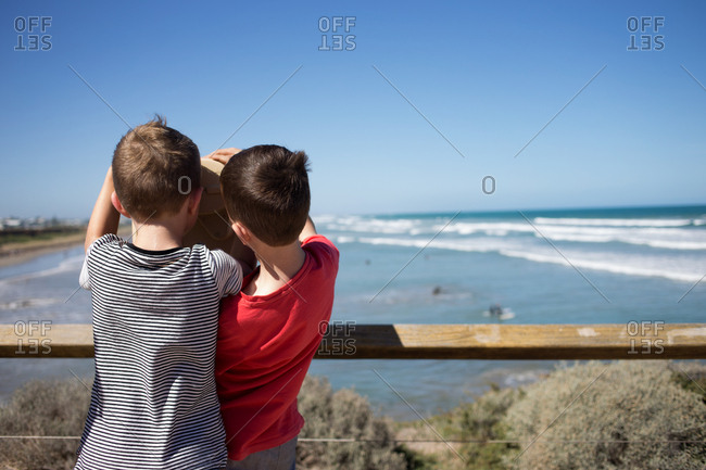 Two brothers looking at ocean together through public binoculars