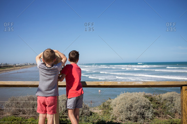 Young boys enjoying ocean view on coastal cliff
