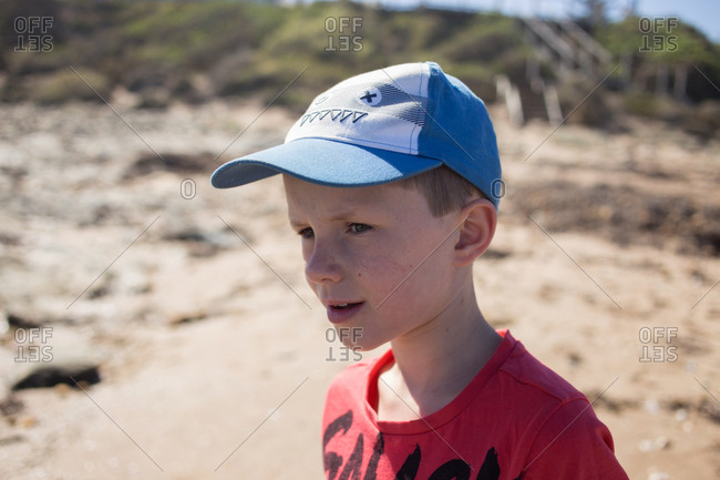 Portrait of young blonde boy wearing ball cap on the sunny beach