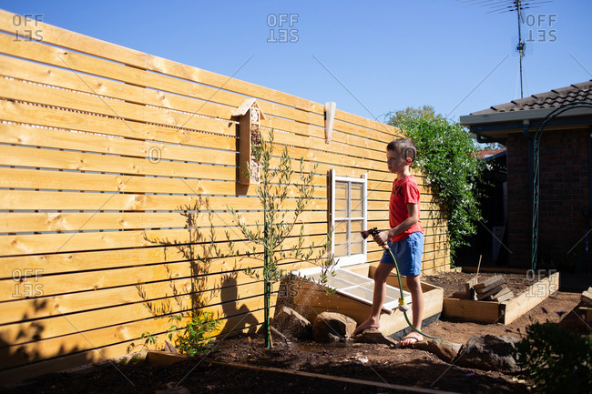 Young boy standing in garden holding water hose