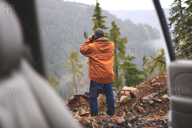 Rearview of man scanning far side of steep valley with binoculars seen through open car door