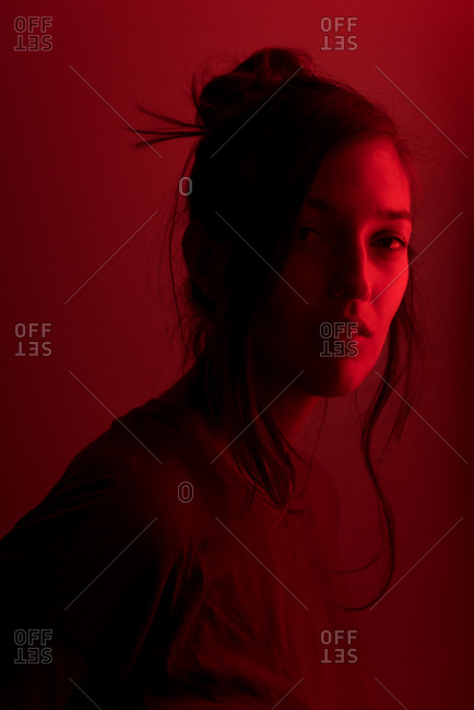 Portrait of a young beautiful woman standing in front of a red neon