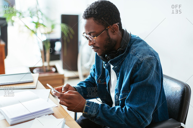 Man using his phone working in creative office