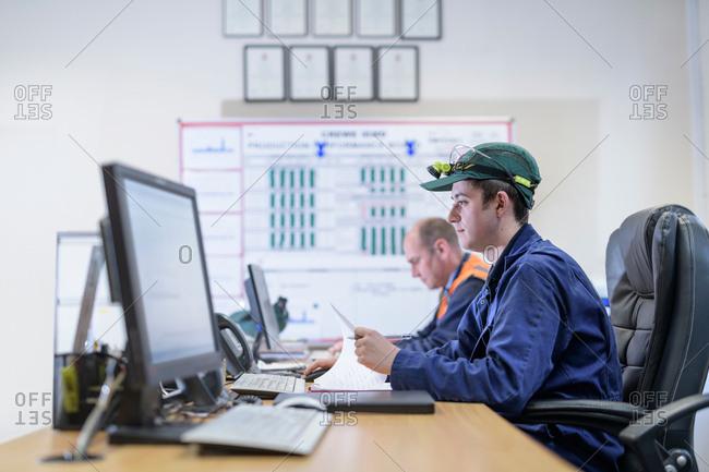 Apprentice engineers in control room in train engineering factory