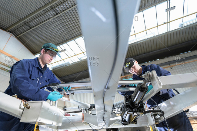 Apprentice engineers working on locomotive pantograph in train engineering factory