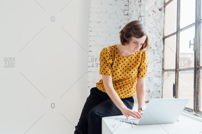 Businesswoman sitting on windowsill using laptop