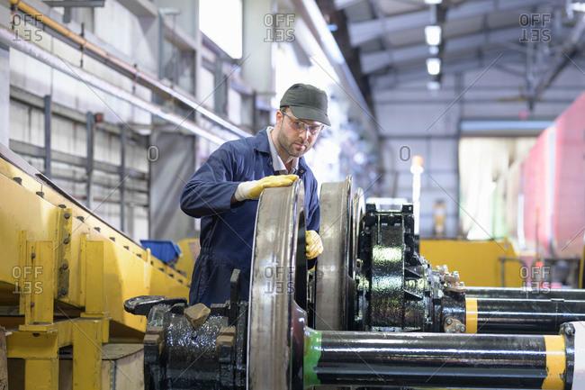 Engineer inspecting locomotive wheels for wear in train engineering factory