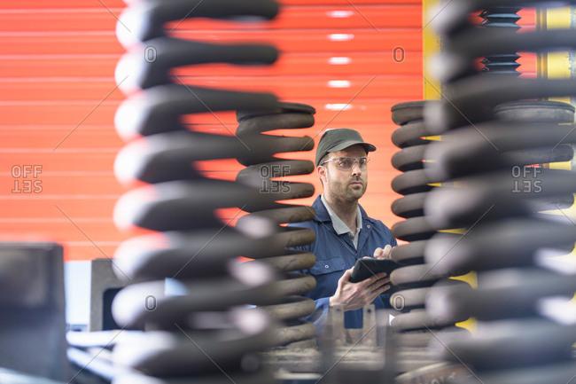 Engineer inspecting springs in train engineering factory