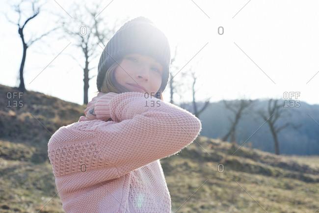 Sunlit portrait of mid adult woman wearing knitted hat in field