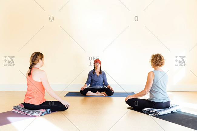 Teacher and women practicing sukhasana yoga pose in yoga studio