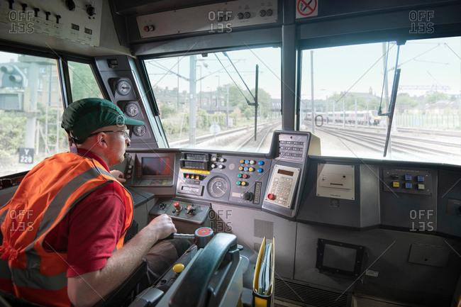 Train driver in stationary locomotive on train tracks