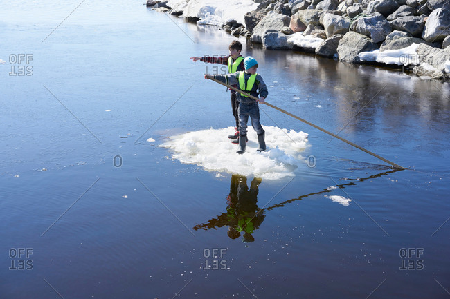 Two boys standing on ice, on lake, pushing themselves along with pole