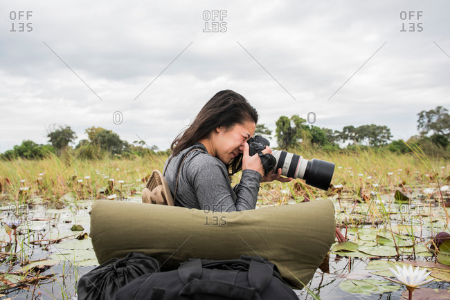 Young female tourist photographing Okavango Delta, Botswana, Africa