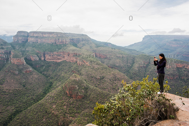 Young female tourist photographing landscape from The Three Rondavels, Mpumalanga, South Africa