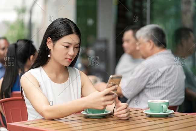 Businesswoman sitting outdoors, at cafe, using smartphone