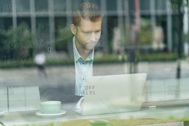 Businessman sitting in cafe, using laptop, viewed through window