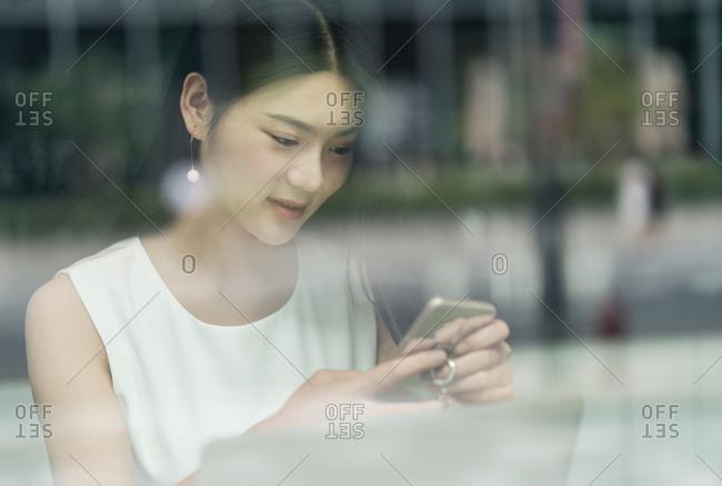Businesswoman using smartphone and laptop, viewed through window