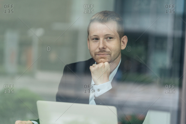 Businessman sitting, laptop in front of him, thoughtful expression, viewed through window