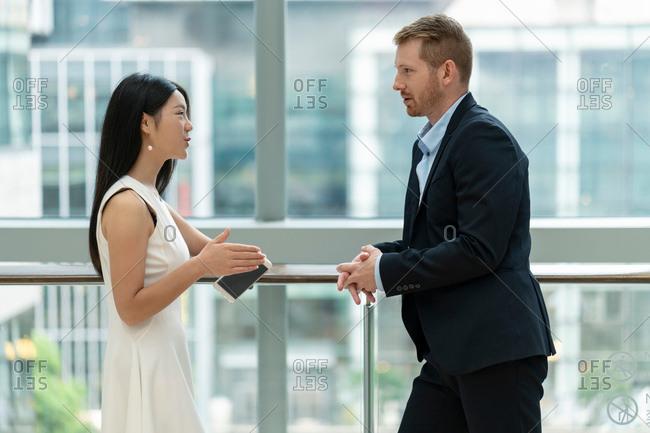 Businessman and businesswoman standing beside window, in conversation