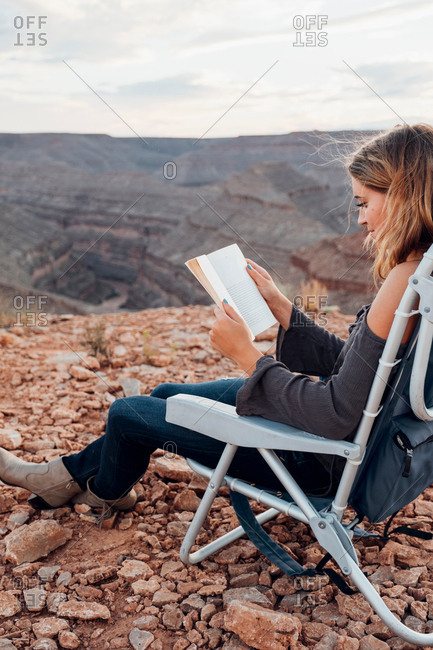 Young woman in remote setting, sitting on camping chair, reading book, Mexican Hat, Utah, USA