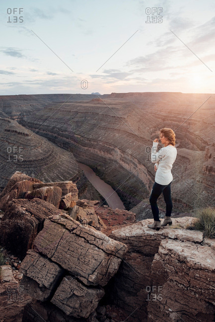 Young woman in remote setting, standing on rocks, looking at view, Mexican Hat, Utah, USA