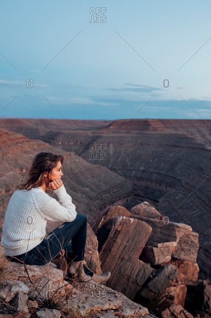 Young woman in remote setting, sitting on rocks, looking at view, Mexican Hat, Utah, USA