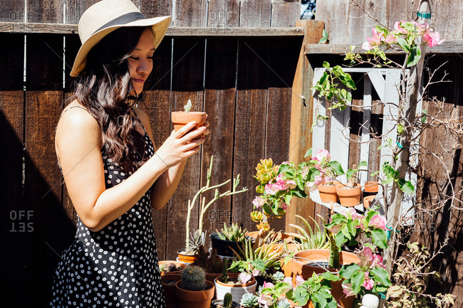 Young woman outdoors, tending to potted plants in garden
