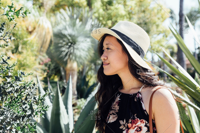 Young woman outdoors, looking at plants in garden