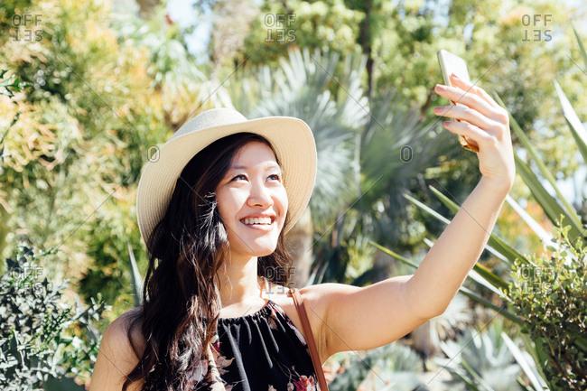 Young woman outdoors, taking selfie in ornamental garden