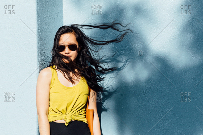 Portrait of young woman outdoors, hair blowing in breeze