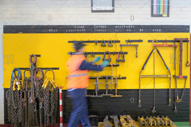 Engineer selecting lifting equipment in train engineering factory