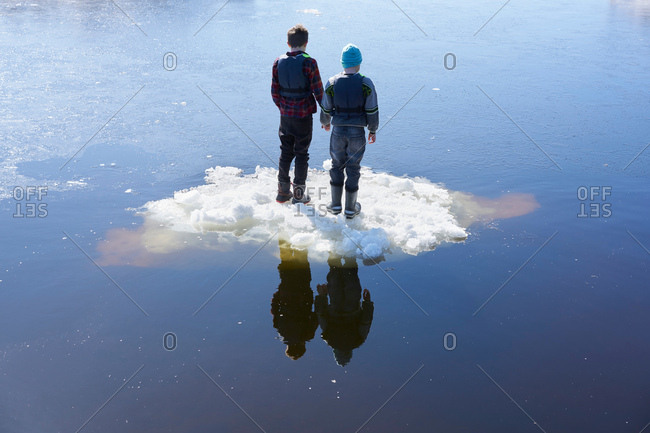 Two boys standing on ice, on lake, rear view