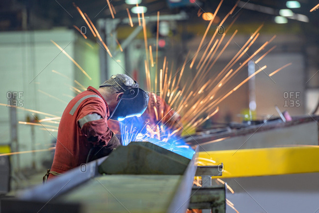 Welder using grinder in trailer factory