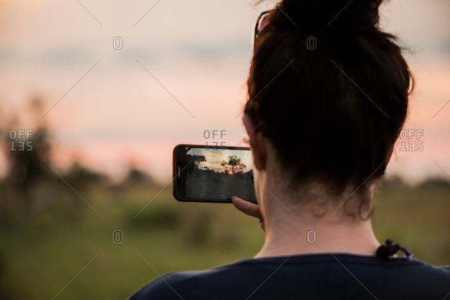 Young woman photographing with smartphone on Okavango Delta, rear view, Botswana, Africa