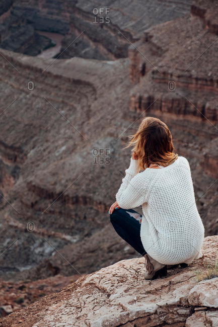 Young woman in remote setting, crouching on rocks, looking at view, rear view, Mexican Hat, Utah, USA