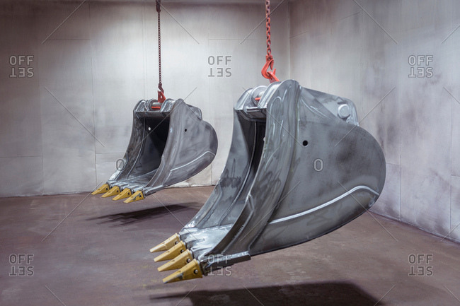 Digger buckets hanging in spray booth in engineering factory