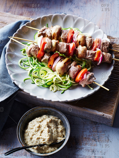 Lamb souvlaki skewers, with courgette noodles and baba ganoush, close-up