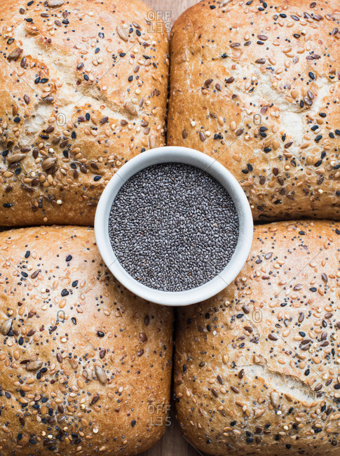 Multigrain bread rolls and bowl of chia seeds, close up overhead view