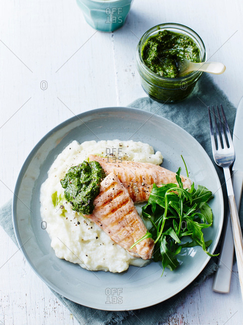 Still life with plate of grilled salmon, rocket and cauliflower puree, overhead view