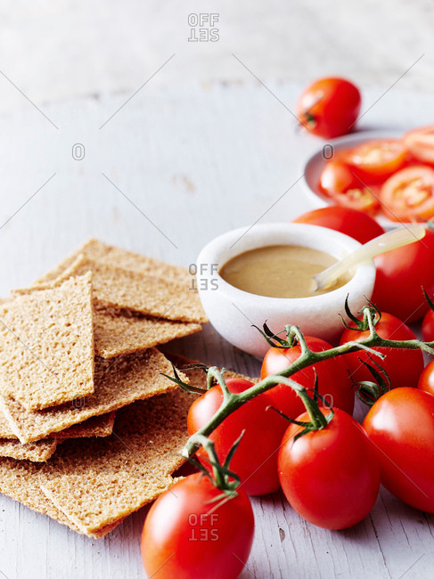 Still life with tahini, rye crackers and vine tomatoes