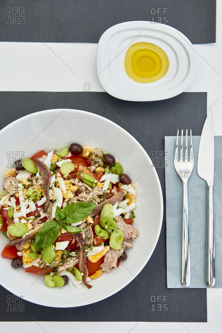 Salade niçoise served on a white plat with a side of olive oil