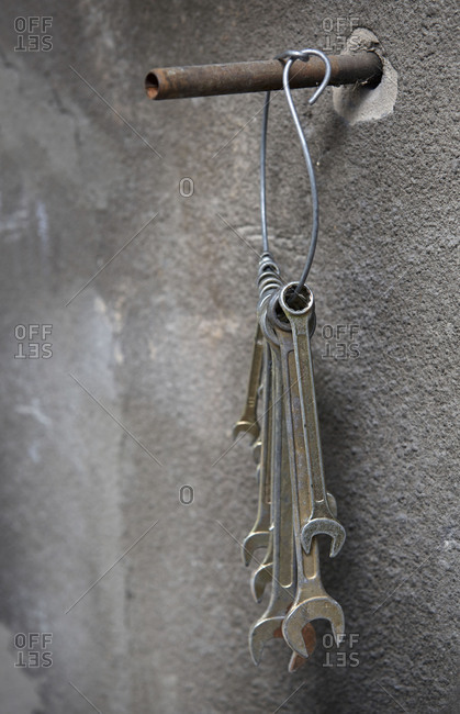 Old wrenches hanged on a concrete wall