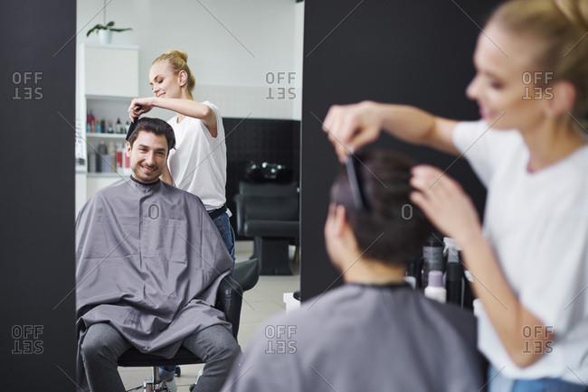 Smiling hairdresser combing man's hair