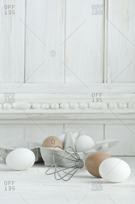 White and brown eggs- wire whisk on wood