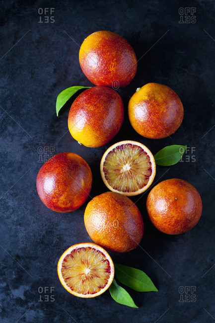 Whole and sliced blood oranges on dark ground