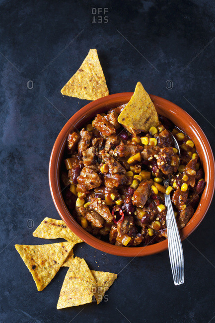 Vegetarian Chili with soy meat cut into strips and tortilla chips in earthenware dish