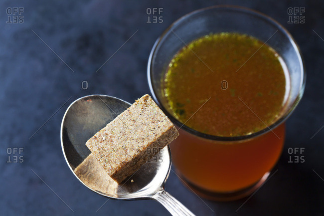 Glass of stock and stock cube on tea spoon