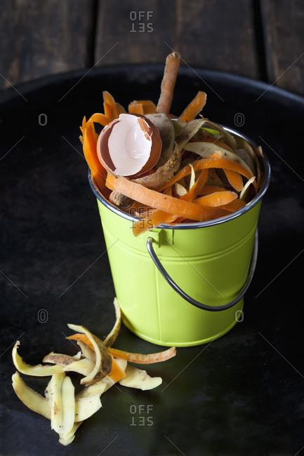 Green metal bucket with organic waste