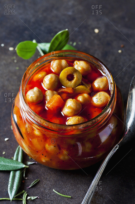 Glass of chick-pea stew with green olives