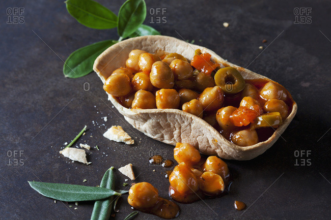 Chick-pea stew with green olives in edible bowl
